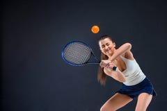 Portrait de beau joueur de tennis de fille avec une raquette sur le fond foncé Photos stock