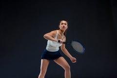 Portrait de beau joueur de tennis de fille avec une raquette sur le fond foncé Photo stock