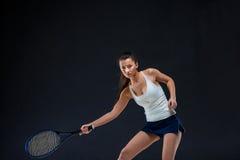 Portrait de beau joueur de tennis de fille avec une raquette sur le fond foncé Images libres de droits
