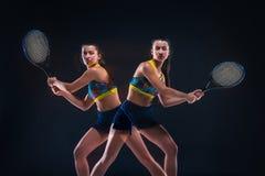 Portrait de beau joueur de tennis de fille avec une raquette sur le fond foncé Image libre de droits