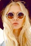 Portrait de beauté d'une blonde sexy avec les lunettes florales rondes, grandes lèvres, cheveux onduleux et chapeau de Bourgogne, image stock