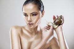 Portrait de beauté d'une jeune femme tenant l'escargot Photographie stock