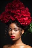 Portrait de beauté d'une jeune jolie fille avec les fleurs rouges sur sa tête Image stock
