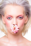 Portrait de beauté de modèle avec la fleur dans sa bouche Photo stock