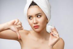 Portrait de beauté de la femme asiatique à moitié nue regardant sur la caméra et tenant la crème de visage sur sa paume d'isoleme image libre de droits