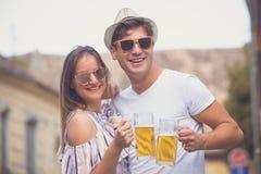 Portrait de beaux couples grillant avec de la bière extérieure Photographie stock