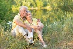 Portrait de beaux couples supérieurs détendant et posant en parc d'été photographie stock libre de droits