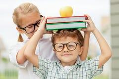 Portrait de bel écolier et de fille regardant très heureux  Photographie stock libre de droits