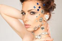 Portrait de belle brune avec des diamants sur son visage Images stock