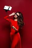 Portrait de belle brune dans la robe impressionnante et des lèvres rouges utilisant des lunettes de soleil tout en faisant le sel Photos stock