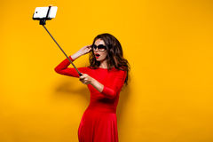 Portrait de belle brune dans la robe impressionnante et des lèvres rouges utilisant des lunettes de soleil tout en faisant le sel Photo stock