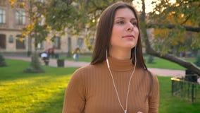 Portrait de belle brune mettant sur des écouteurs et dansant en musique sur le fond vert de parc clips vidéos