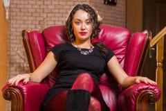 Portrait de belle brune romantique sur une chaise rouge Photographie stock libre de droits