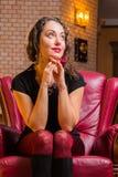 Portrait de belle brune romantique sur une chaise rouge Photo libre de droits
