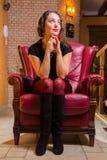 Portrait de belle brune romantique sur une chaise rouge Images libres de droits