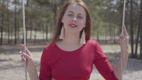 Portrait de belle femme élégante dans la robe rouge qui se reposent dans la forêt sur l'oscillation et regarder un spectaculaire  banque de vidéos