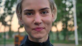 Portrait de belle femme blonde avec le nez percé regardant l'appareil-photo et souriant, inclinant la tête d'accord, parc dedans clips vidéos