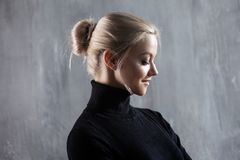 Portrait de belle femme blonde Calme et confiance en soi Belle fille adulte dans le col roulé noir, fond gris Photo stock