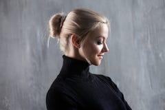Portrait de belle femme blonde Calme et confiance en soi Belle fille adulte dans le col roulé noir, fond gris Photographie stock libre de droits