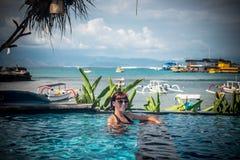 Portrait de belle femme bronzée dans des vêtements de bain noirs détendant dans la station thermale de piscine Jour d'été chaud e Images libres de droits