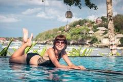 Portrait de belle femme bronzée dans des vêtements de bain noirs détendant dans la station thermale de piscine Jour d'été chaud e Images stock