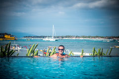 Portrait de belle femme bronzée dans des vêtements de bain noirs détendant dans la station thermale de piscine Jour d'été chaud e Photos stock