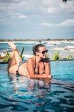 Portrait de belle femme bronzée dans des vêtements de bain noirs détendant dans la station thermale de piscine Jour d'été chaud e Photo libre de droits