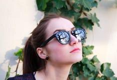 Portrait de belle femme dans des lunettes de soleil noires Photographie stock