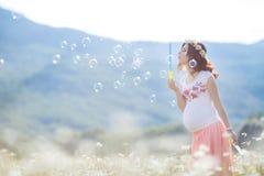 Portrait de belle femme enceinte dans les bulles de soufflement de champ image stock