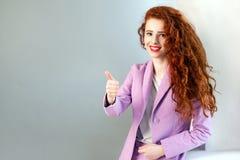 Portrait de belle femme heureuse réussie d'affaires avec les cheveux rouge-brun et de maquillage dans le costume rose avec des po Photographie stock