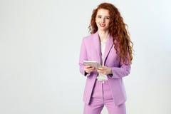 Portrait de belle femme heureuse réussie d'affaires avec les cheveux rouge-brun et de maquillage dans le costume rose tenant le c images stock
