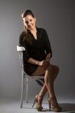 Portrait de belle femme posant dans le studio sur chear Image libre de droits