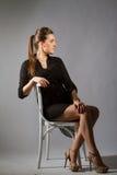 Portrait de belle femme posant dans le studio sur chear Photos libres de droits
