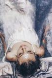 Portrait de belle femme se situant dans l'eau avec le tissu Mode photo stock