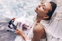 Portrait de belle femme se situant dans l'eau avec le tissu Mode photographie stock