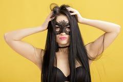 Portrait de belle femme sensuelle dans le masque noir de dentelle sur le fond jaune Fille sexy dans le masque vénitien Photographie stock