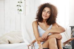 Portrait de belle fille africaine rêveuse dans se reposer de sourire de vêtements de nuit dans la chaise à la maison Copiez l'esp Photo stock
