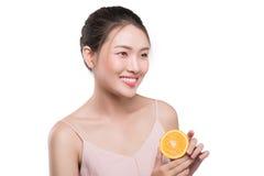 Portrait de belle fille asiatique avec les cheveux noirs tenant l'orange Photos stock