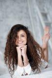 Portrait de belle fille avec les cheveux bouclés sur le lit Images libres de droits