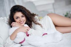 Portrait de belle fille avec les cheveux bouclés sur le lit Photos libres de droits
