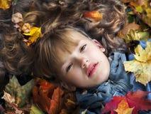 Portrait de belle fille dans des feuilles d'automne Image stock