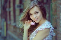 Portrait de belle fille dans une robe près de mur de briques avec un thé Photo stock