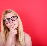 Portrait de belle fille recherchant sur le fond rouge Photographie stock