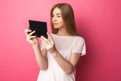 Portrait de belle fille regardant dans le miroir, s'admirant, sur le fond rose, heureux et mignon photos libres de droits