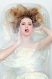 Portrait de belle fille sensuelle de jeune femme blonde séduisante avec du charme dans l'eau brillante regardant l'appareil-photo Image stock