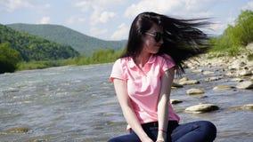 Portrait de belle jeune dame de sourire avec les verres ronds et les cheveux ondulant sur le vent Rivière de montagne carpathienn Photos stock