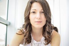 Portrait de belle jeune femme à la fenêtre Photographie stock libre de droits