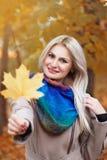 Portrait de belle jeune femme blonde avec la feuille d'érable Photo stock