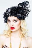 Portrait de belle jeune femme blonde dans le chapeau exagéré sur le fond blanc photo stock