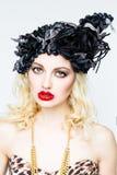 Portrait de belle jeune femme blonde dans le chapeau exagéré sur le fond blanc photographie stock